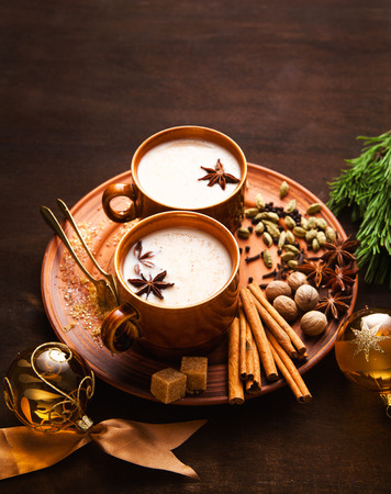 Masala tea chai latte traditional hot Indian teatime ceremony sweet milk with spices, herbs organic infusion healthy beverage in porcelain cup on wooden table background. Christmas style. New Years decorations