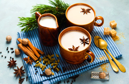 Masala tea chai latte traditional hot Indian teatime ceremony sweet milk with spices, herbs organic infusion healthy beverage in porcelain cup on blue table background Stock Photo
