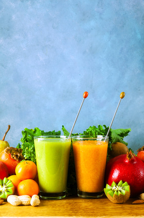 Freshly blended fruit smoothies of various colors and tastes in glass  in wooden tray. Yellow, green. on wooden table and blue background Zdjęcie Seryjne