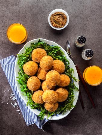 이탈리아 간식. 쌀에서 튀긴 공 Arancini 버섯, 치즈와 겨자 소스와 갓 압착 된 오렌지 주스와 회색 돌 테이블에 rucola의 샐러드. 빠른 건강한 왕성한 식사 스톡 콘텐츠