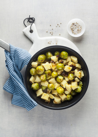 Italian gnocchi from potatoes with Brussels sprouts and walnuts in a frying pan on a white marble cutting board on a stone kitchen table. classic healthy recipes Stok Fotoğraf