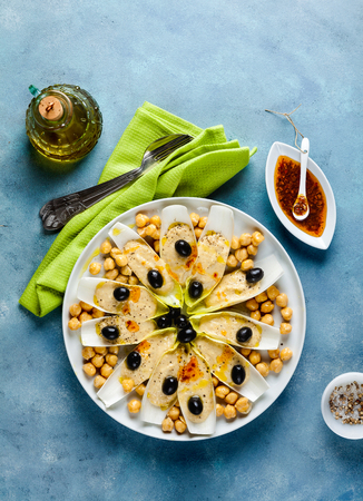 The leaves of Belgian endive with hummus, chickpeas and black olives. With strong olive oil of red pepperoncino. Modern delicious food for vegetarians and gourmets.