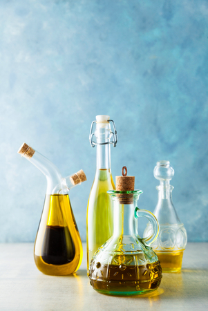 different shapes, types and sizes of cruets with olive oil on the table on blue