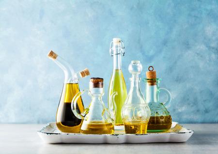 różne kształty, rodzaje i rozmiary ampułek z oliwą na stole na tacy na niebiesko