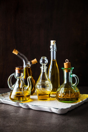 Different shapes, types and sizes of cruets with olive oil on the table on a tray on dark