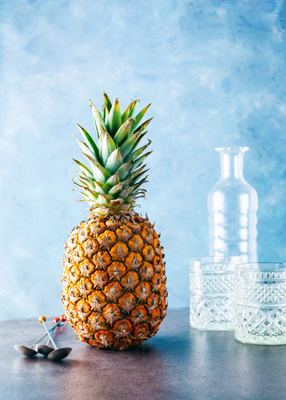 a whole ripe Pineapple on the table and a glass bottle with beautiful glasses. long spoons of a bartender. preparation of Cocktail  or freshly squeezed juice on blue