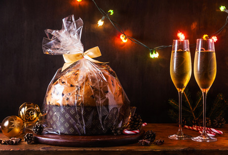 Italian festive bread panetton with a transparent wrapper on a table decorated for Christmas. and two glasses of champagne. New Years traditional dessert