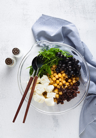 healthy vegan lunch bowl. chickpeas, sun-dried tomatoes, feta cheese or tofu, arugula and black olives vegetables salad. Top view