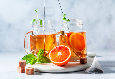 Traditional iced tea with orange and mint and ice in mason jars . refreshing summer drink on white marble board