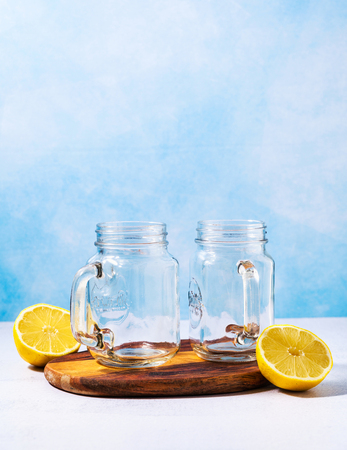 two glass cup with handle. ready for making cooling drinks or freshly squeezed juices and two halves of lemon. copy space