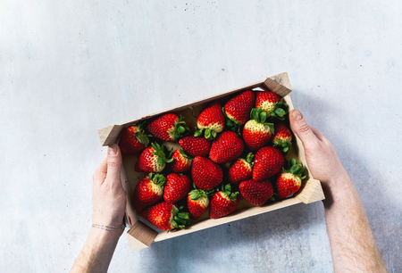 mens hands hold a wooden box with Pile of juicy ripe organic strawberries . sale on the market