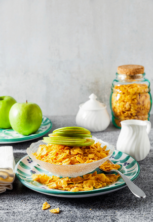 Cornflake cereals in a bowl with milk and a green apple , quick breakfast Stock Photo