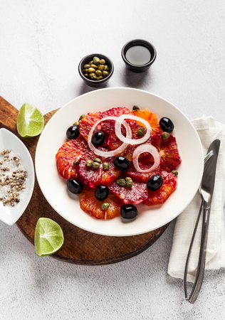 typical Spanish-style salad of red orange, onion and olives with capers and fresh raw olive oil and lime juice . Served on a stone white table. summer healthy snack or light lunch