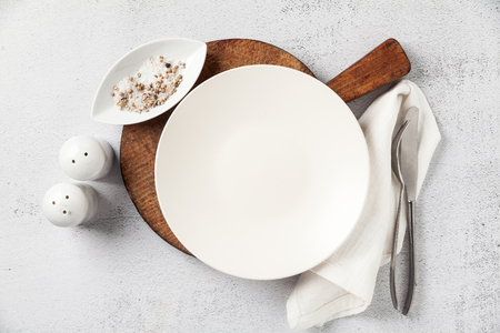 empty plate and cutlery on a wooden cutting board. a fork, a knife and a salt bowl with a pepper shaker. on white stone background, napkin. the table is set for breakfast or lunch Standard-Bild