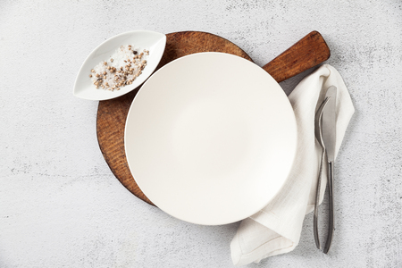 empty plate and cutlery on a wooden cutting board. a fork, a knife and a salt bowl with a pepper shaker. on white stone background, napkin. the table is set for breakfast or lunch Banco de Imagens