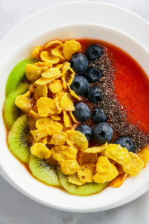 a bowl of smoothies, with cereals for a healthy breakfast and berries, chia seeds and coconut chips freshly sliced fruit, Wheat bran and Cornflake. Served with a wooden spoon on a white marble table. close up