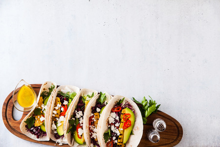 Mexican tacos with avocado, grilled corn, red cabbage slaw and chili salsa on wooden board black shale table. Recipe for Cinco de Mayo party. Top view. Copy space background Stock Photo