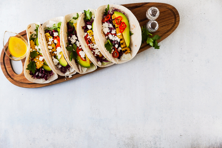 Mexican tacos with avocado, grilled corn, red cabbage slaw and chili salsa on wooden board black shale table. Recipe for Cinco de Mayo party. Top view. Copy space background 写真素材