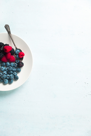 Fruit salad with Various fresh summer berries in white plate . Top view Standard-Bild