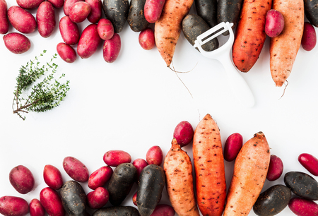 Different varieties in form and color of potatoes  on a white isolated background. red, Shetland Black potato and sweet