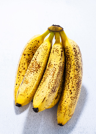 branch of overripe bananas with black dots on the table. natural sweetener. concept of a healthy lifestyle