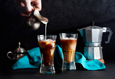 a man's hand pours milk in cold brew coffee on the table. coffee pot in the background