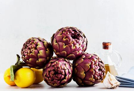 Fresh bunch of purple artichokes on white background with lemon, olive oil , garlic . spring healthy food Reklamní fotografie