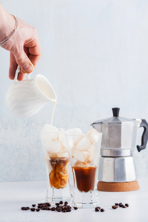 Mans hand pours milk on Iced coffee , beautiful and clean composition. coffee maker on back