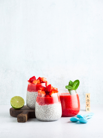 morning breakfast desserts in glasses. pudding from seeds of chia and coconut milk and puree from ripe strawberry. a light summer snack for children or athletes. Dietary healthy food.