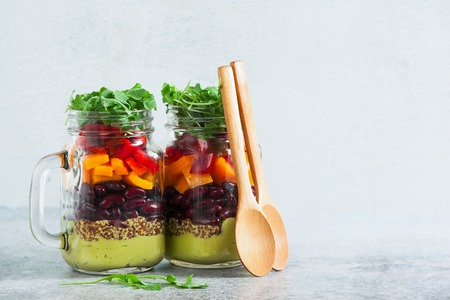 rainbow colored salad in jars on the table. with beans, fresh vegetables and avocado dressing with lime juice and mustard. copy space. Stock Photo