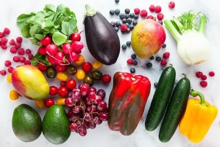 colorful fruits, vegetables and berries scattered on a table of white marble. background eating healthy food Banque d'images