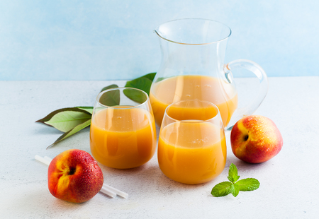 peach juice in glasses and a decanter and fresh peaches with leaves on a table. blue background. copy space Stock Photo