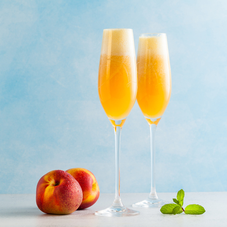 two glasses of champagne with a cocktail of Bellini and fresh peaches on a blue background. summer refreshing drink 版權商用圖片