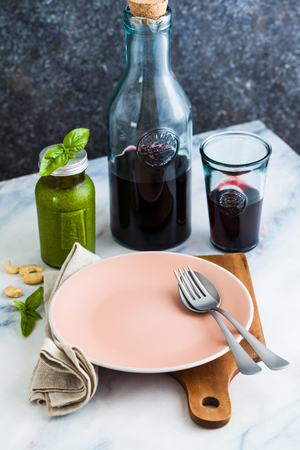 Red wine in the bottle and recycled glassware on the table. fresh grapes, bread and cheese. Mediterranean food