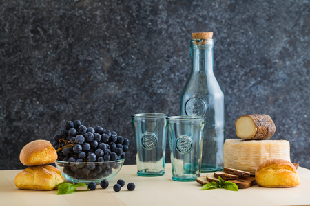 glassware and bottle of recycled glass for wine on the table with cheese, grape and bread 免版税图像