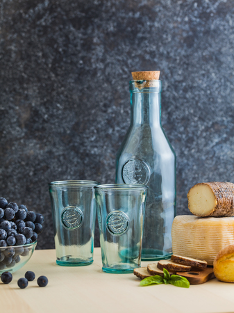 glassware and bottle of recycled glass for wine on the table with cheese, grape and bread Фото со стока