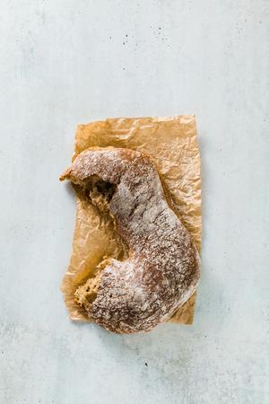 a piece of fresh rye italian  bread on the table.