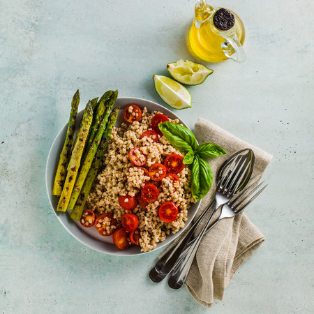 salad from gluten-free sorghum ( great millet ), grilled asparagus and cherry tomatoes with tahini sesame pasta sauce and lime juice in a plate on the table. Healthy vegan cuisine for patients with celiac disease