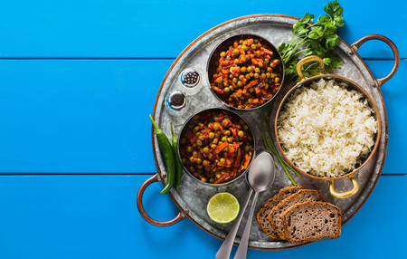 vegan curry with green peas and basmati rice served on a blue table tray, healthy Indian comfort food, copy space