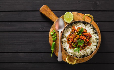 vegan curry with green peas and basmati rice served on a wooden table tray, healthy Indian comfort food