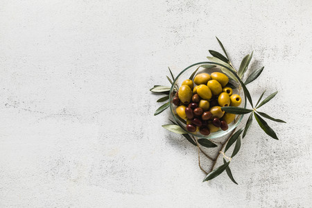 assortment of olives in a transparent bowl and a branch of olive tree. snack or appetizer. hors doeuvre Stock Photo