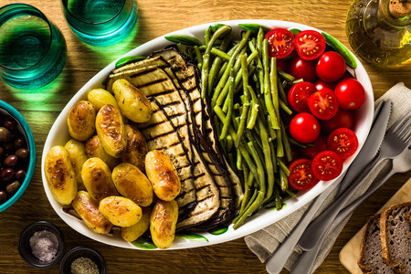 a side dish of vegetables on the holiday table. healthy food for the whole family or dinner at a restaurant on a wooden table. baked potatoes, grilled eggplants, cherry tomato salad and steamed green beans with garlic sauce.
