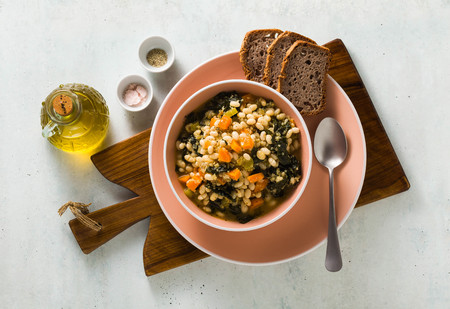 winter warming soup with kale and beans on the table with whole grain bread. healthy vegan food