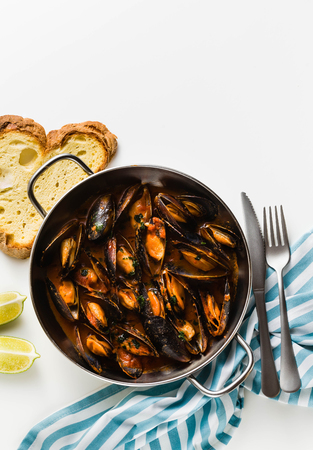 freshly cooked mussels in a frying pan in tomato sauce. pepata di cozze or mussels marinara. classic dish of mediterranean italian cuisine . isolated on white