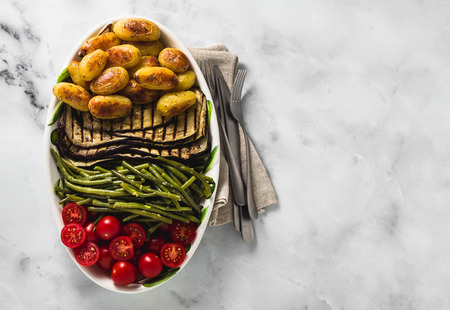 a side dish of vegetables on the holiday table. healthy food for the whole family or dinner at a restaurant on a white marble table. baked potatoes, grilled eggplants, cherry tomato salad and steamed green beans with garlic sauce.
