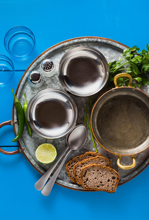 table served in Indian style. Tin tray with copper pan and empty metal bowls plate on a blue wooden table. copy space Stock Photo
