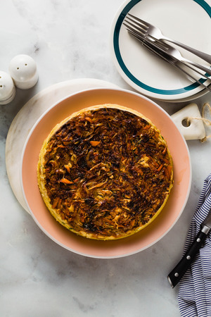 savory salty  Upside-Down pie from white cabbage, carrots and onions. gluten free no eggs , with chickpea flour. family breakfast or party snack on a white marble table