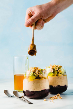 Vegan layered banana dessert of green buckwheat, chia seeds and quinoa with blueberry jam in a glass with fresh fruits, nuts and honey. healthy morning meal for breakfast. Banque d'images