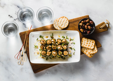 vegan appetizer of grilled zucchini and olive pate on a festive table. healthy food for a family or a party Banco de Imagens
