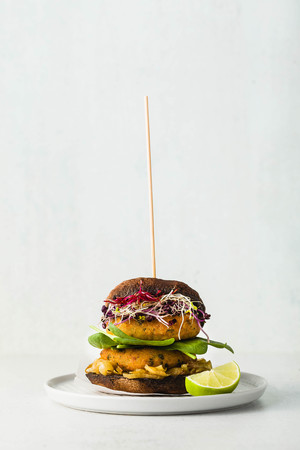 Gluten-free vegan burger made from portobello mushrooms with cutlets from potato and chickpea flour with caramelized onions, sprouts and baby spinach. Healthy fast food made from natural products
